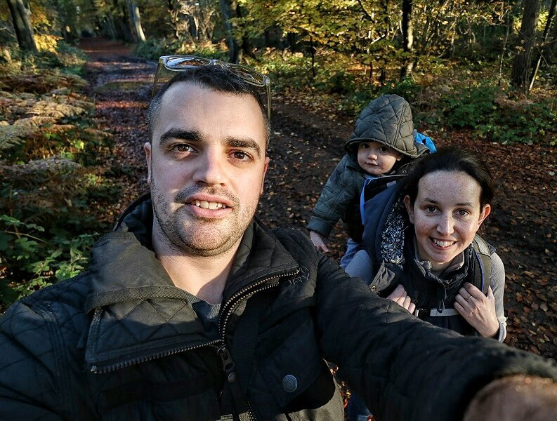 A selfie of a mother and father out walking in the countryside, the mum has their baby on her back in a carrier