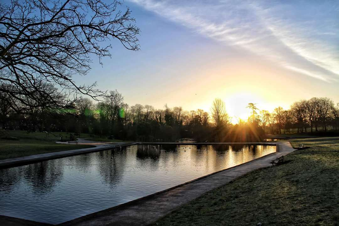 The sun sets over an ornamental lake in a park