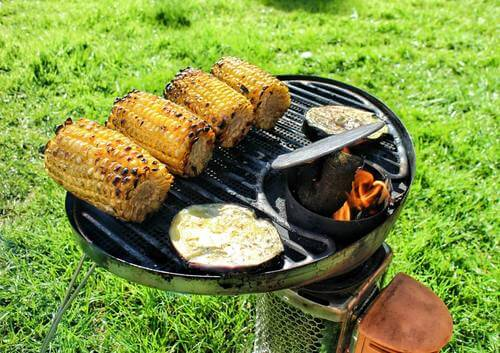 vegetarian food for camping including corn on the cob and aubergine is cooking on a camping stove