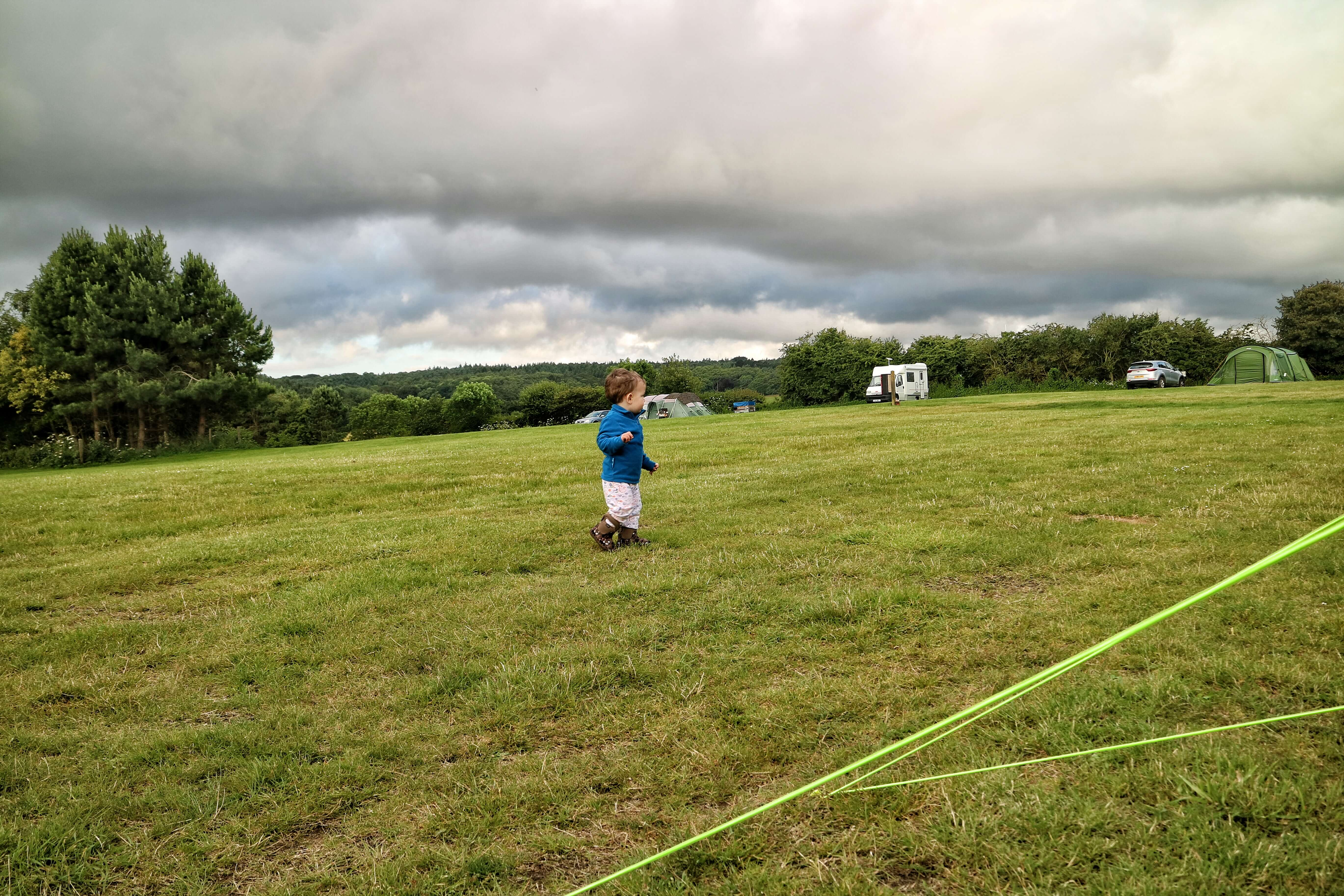 A toddler runs around a campsite