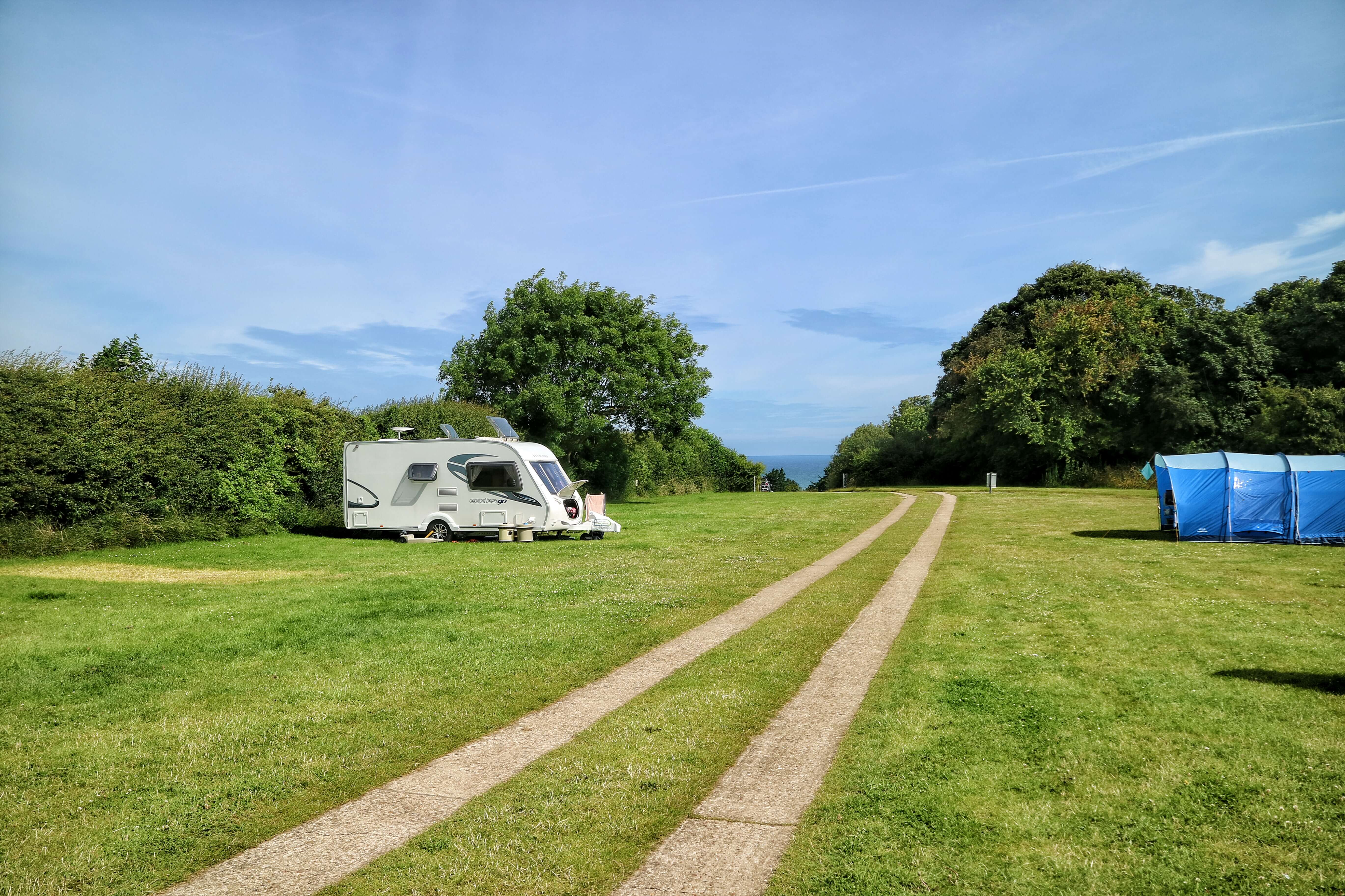 A track through a campsite. There is a caravan and tent either side. In the distance you can see the sea.