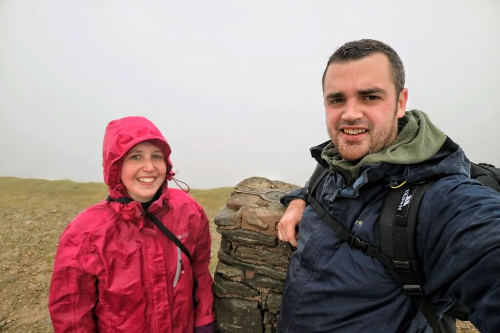 A couple at a trig point on the summit of Helvellyn in the rain