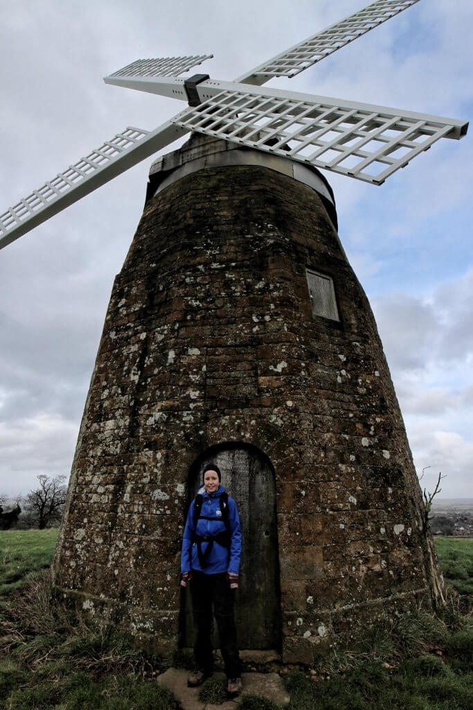A woman in a blue coat sands in front of a windmill