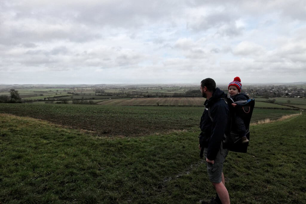 A man carries a toddler in a carrier on his back, they are on a hill looking over the countryside