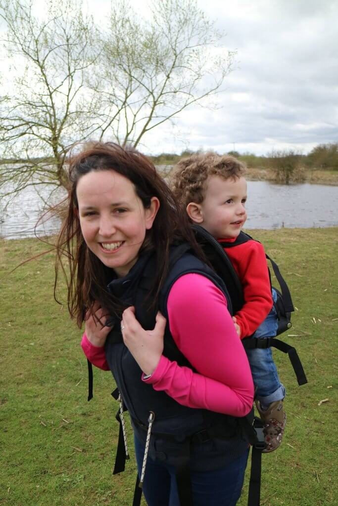 A smiling woman looks at the camera, her child is on her back in a carrier looking way. There is a lake in the background