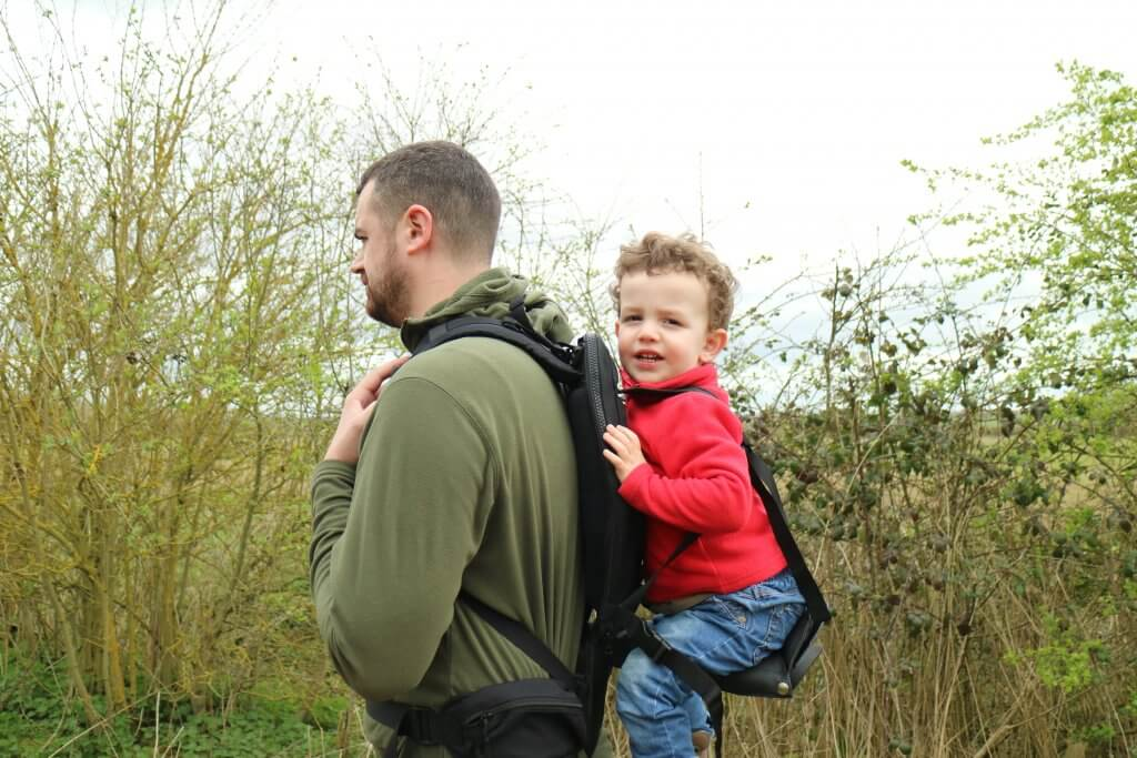 A man in the outdoors with a toddler in a carrier on his back
