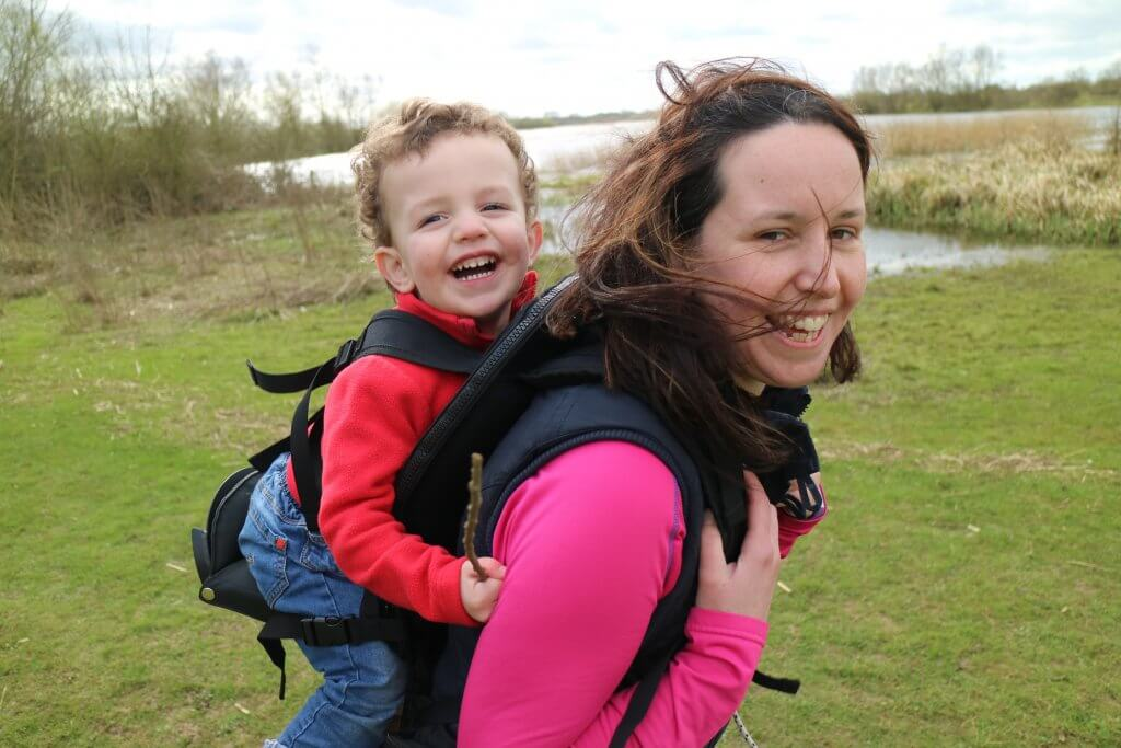 A laughing woman is walking beside a lake in the countryside, she has a laughing toddler on her back in a carrier