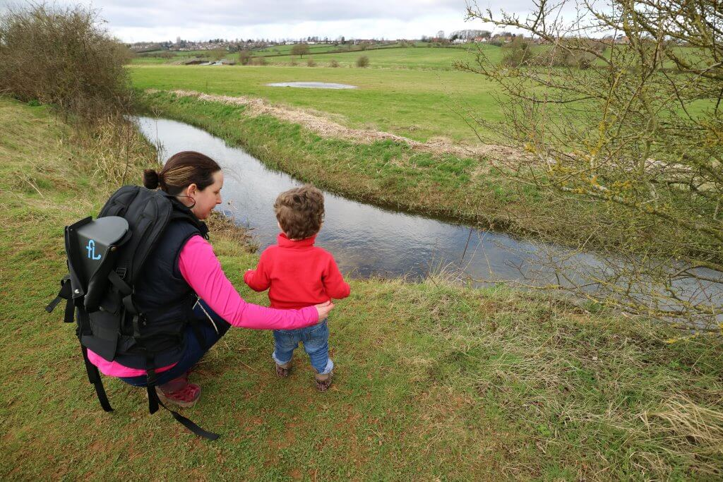 A mother and her toddler son look out over fields and a river