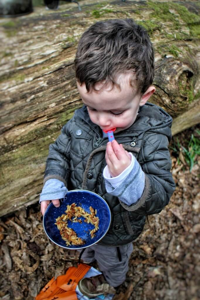 A young boy eats some pasta from a bowl. He is outdoors, standing by a fallen log