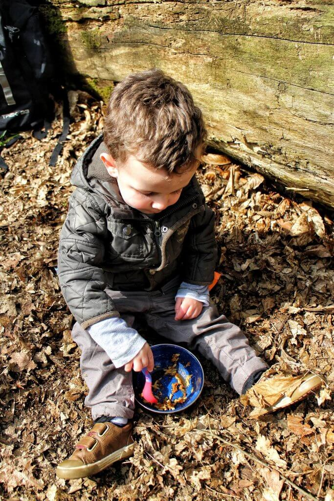 A young boy sits on a forest floor, eating pasta from a bowl