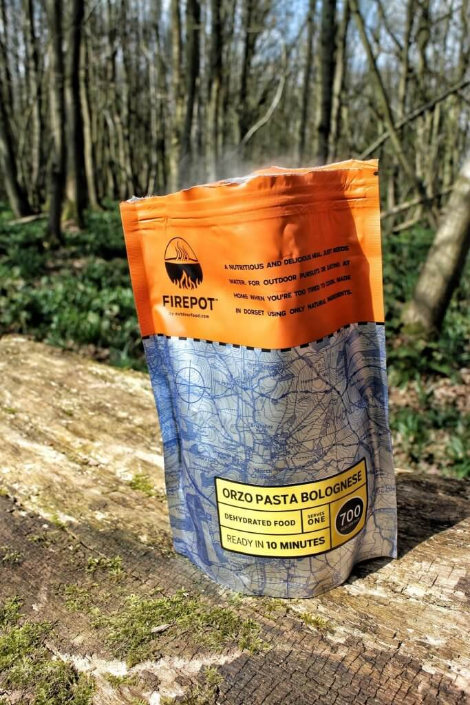 A pack of dehydrated food, after hot after has been added. There is a forest in the back ground