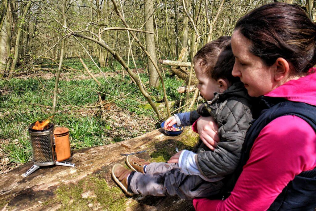 A woman and toddler look at a camping stove. They are in a forest