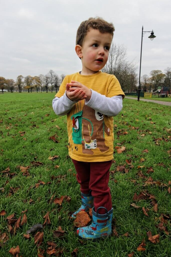 a boy stands in a field with a yellow top, red joggers and blue wellies