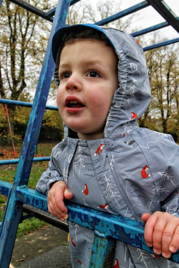 a boy wearing a raincoat stands on a climbing frame and looks out to the distance