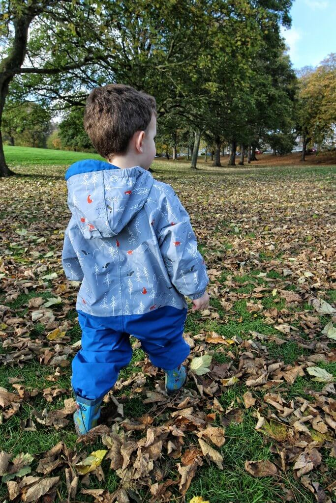 a smal boy in a blue and grey rainsuit walks away from the camera in a large park